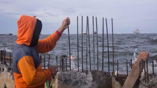 A worker constructing Jakarta's giant sea wall in Muara, North Jakarta in Indonesia.
