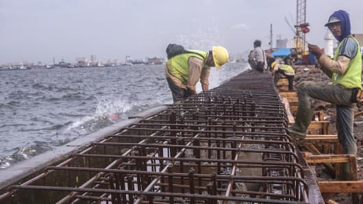 Workers constructing Jakarta's new giant sea wall.