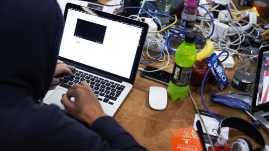 An attendee wearing a hooded top and working on an Apple Inc. laptop computer participates in the TechCrunch Disrupt London 2015 Hackathon in London