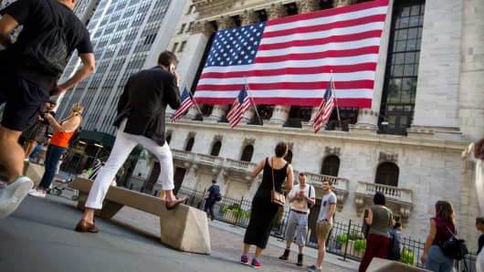 Pedestrians walk past the New York Stock Exchange in New York.
