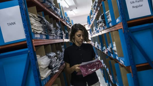An employee collects a customer order from a product aisle at the Grana warehouse.
