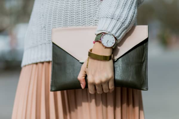 Woman with a watch and a clutch bag
