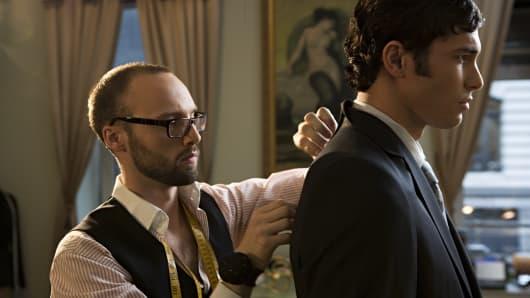 Tailor adjusting man's suit