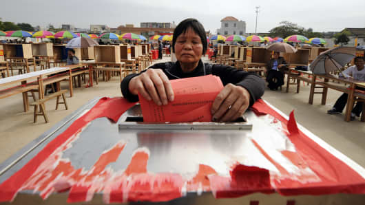 A resident casts her vote on the second day of village elections in Wukan in China's southern Guangdong province on March 4, 2012