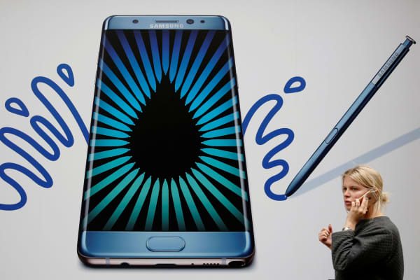 A woman speaks on an Apple phone as she passes an advertisement for the Samsung Galaxy Note 7 in London, September 2, 2016.