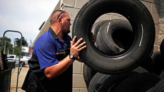 A mechanic stacks used tires outside the service bay of a Goodyear Tire & Rubber Co. auto garage in Shelbyville, Kentucky.