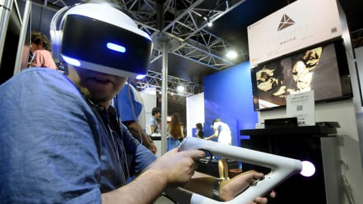 A journalist wearing a PlayStation VR head-mounted display plays a virtual reality game at Sony's booth at the Tokyo Game Show 2016 in Chiba, Japan, on September 15, 2016.