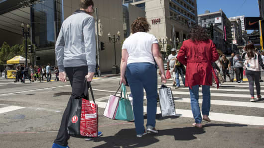Shoppers carry bags while crossing the street near an Apple store in San Francisco.