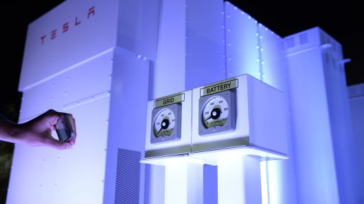 A guests takes photographs of the Powerpack system after Elon Musk, CEO of Tesla unveiled suit of batteries for homes, businesses, and utilities at Tesla Design Studio April 30, 2015 in Hawthorne, California.