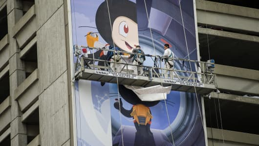 Workers install a billboard for GitHub Inc.