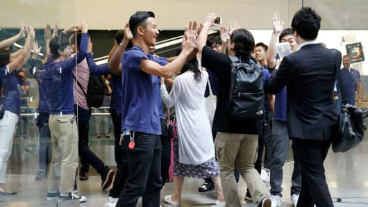 Apple Store staff share high-fives with customers who have been waiting in line to purchase Apple's new iPhone 7 and 7 Plus at an Apple Store in Tokyo, Japan, September 16, 2016.
