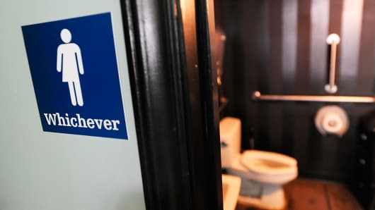 A file photo showing a gender neutral sign posted outside a bathroom at Oval Park Grill on May 11, 2016 in Durham, North Carolina.
