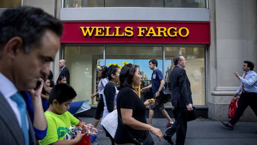 Pedestrians pass in front of a Wells Fargo & Co. bank branch in New York, U.S.