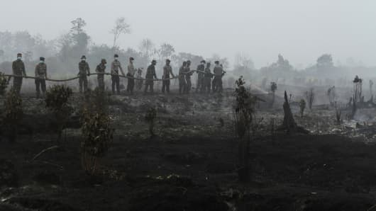 Indonesian police and military personnel extinguish fire in Kampar, Riau province on August 29, 2016.