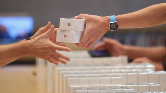 An Apple employee hands over Apple iPhone 7 phones at an Apple store on Sept. 16, 2016 in Berlin.
