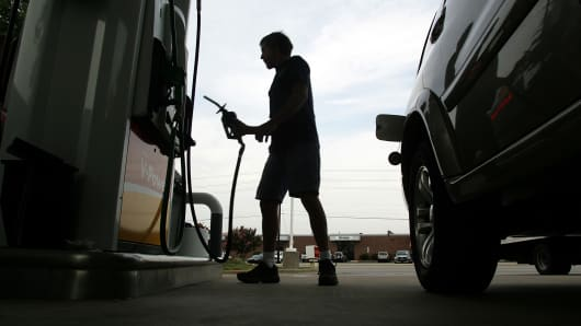 A driver returns the gas nozzle after filling his van at a station in Raleigh, N.C.