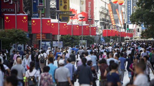 Pedestrians walk past Chinese national flags displayed along Nanjing Road in Shanghai, China.