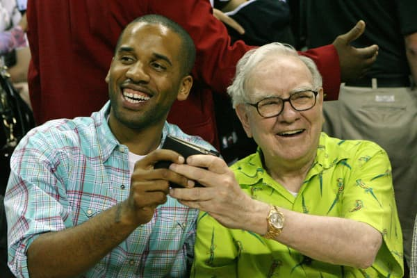 Maverick Carter (L) and Warren Buffett joke around courtside with Buffett's wallet.