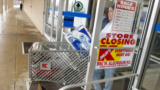 A shopper exits a Kmart store scheduled for closing.