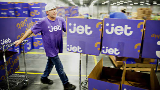 An employee pushes carts of empty boxes for customer orders at the Jet.com Inc. fulfillment center in Kansas City, Kansas.