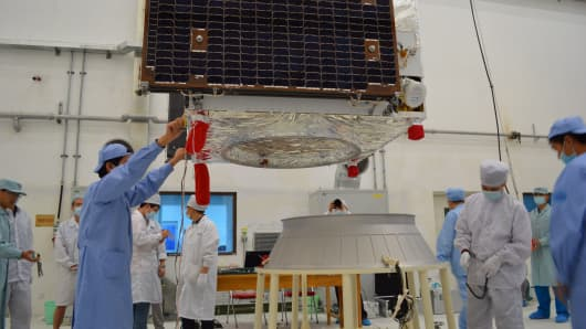 In a separate quantum communications experiment, technical staff dock an experimental quantum communication satellite on a rocket adaptor in Jiuquan, Gansu province, China.