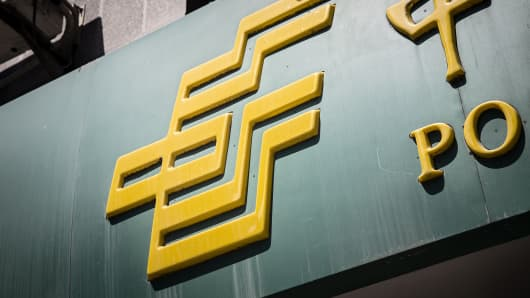 The logo for Postal Savings Bank of China Co. is displayed outside a bank branch in Shanghai, China.