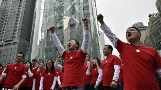 Apple Store employees cheer during the grand opening of an Apple Store in Jiefangbei, Yuzhong District on January 31, 2015 in Chongqing, Sichuan province of China.