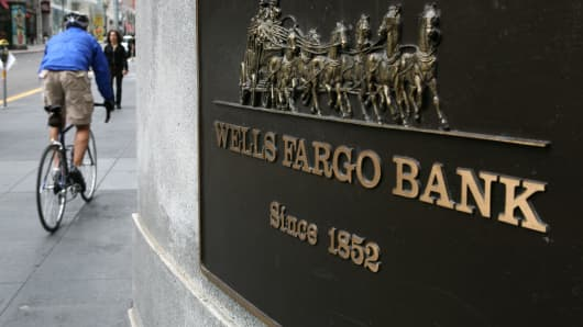 A bicyclist rides by a Wells Fargo bank branch in San Francisco, California.
