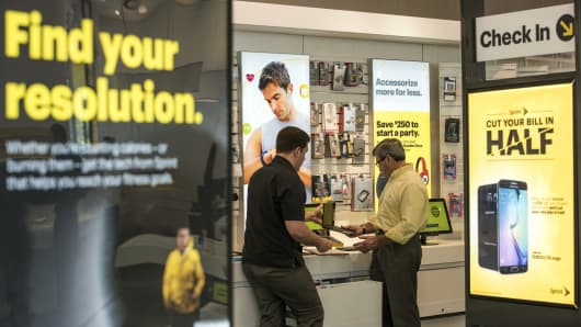 A customer, right, looks at merchandise with an employee at a Sprint Corp. store in Palo Alto, California.