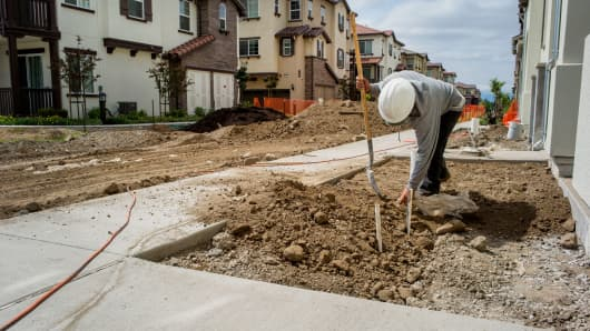 A contractor shovels dirt in front of a townhouse under construction at a Pulte Homes development in San Jose, California.