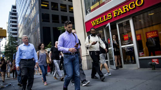 Pedestrians pass in front of a Wells Fargo bank branch in New York.