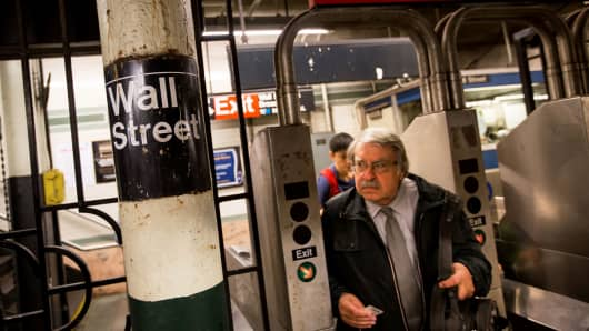 A man passes through a turnstile at the Wall Street subway station near the New York Stock Exchange.