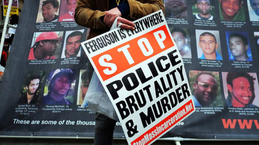 A protester displays a placard at the Union Square in New York on April 14, 2015 during a demonstration against police brutality.