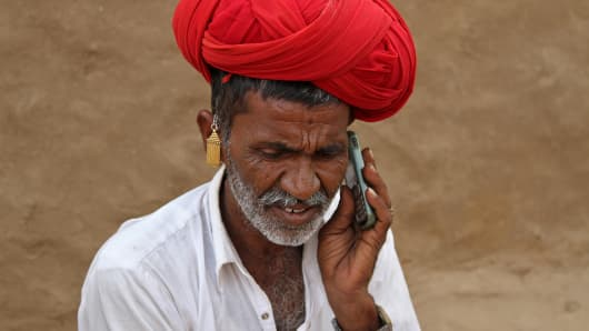 A man talks on his mobile phone in the village of Devmali in the desert state of Rajasthan, India June 14, 2016.