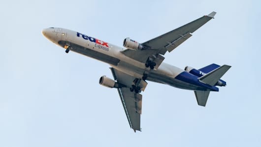 Fedex plane taking off in blue sky. FedEx Corporation is an American global courier delivery services company headquartered in Memphis, Tennessee.