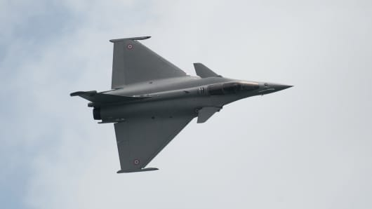 A French fighter jet, the Dassault Rafale, performs an aerial display.