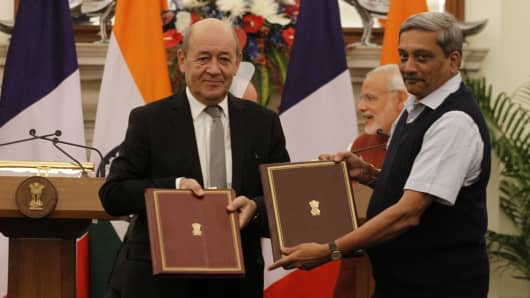 French Defence Minister Jean-Yves Le Drian (2nd L) and his Indian counterpart Manohar Parrikar (R) shake hands as they exchange intergovernmental agreements for the purchase of 36 Rafale jet fighters on January 25, 2016 in New Delhi, India.