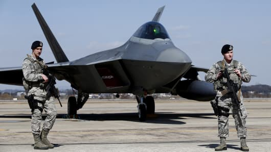 U.S. soldiers stand guard near a U.S. F-22 stealth fighter.