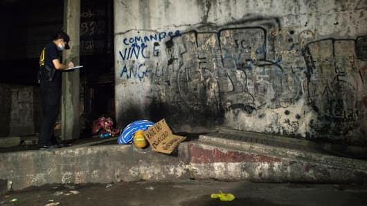 September 21, 2016, Manila: Police forensic teams examine the body of an execution victim, whose head was wrapped in packaging tape. A cardboard sketch next to the corpse read 'Kage Lao Drug Lord of Mindanao.'