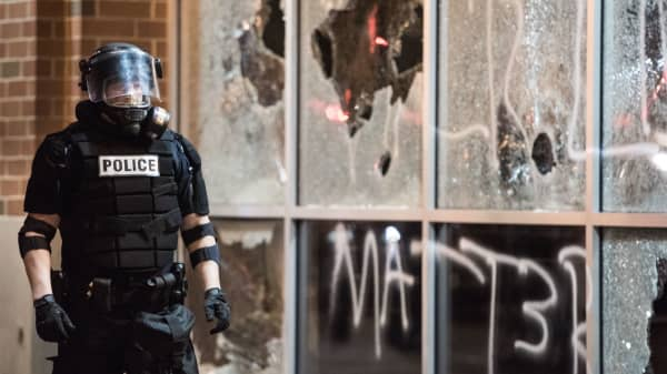 A police officer in riot gear stands near a damaged storefront September 21, 2016 in downtown Charlotte, NC.