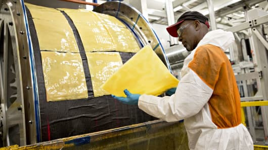 An employee holds a resin tile as a composite engine case mold is prepared for bulk infusion molding at the GE Aviation manufacturing facility in Batesville, Mississippi.