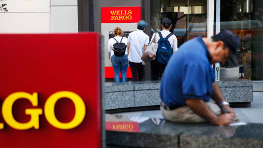 Customers wait for an ATM outside of a Wells Fargo bank branch in Los Angeles.