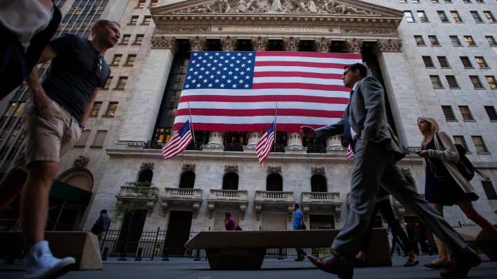 Pedestrians walk past an American flag displayed outside of the New York Stock Exchange (NYSE) in New York.