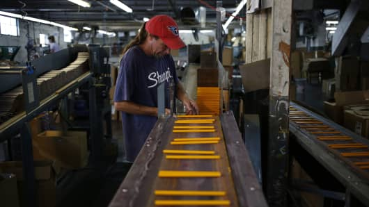 A worker monitors a yellow pencil production line at the Musgrave Pencil facility in Shelbyville, Tennessee.