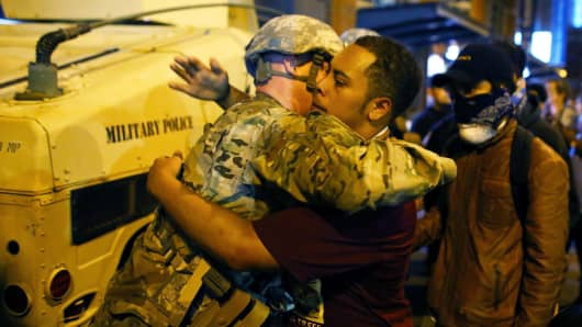 A U.S. National guard soldier accepts a hug from protester as people march through downtown to protest the police shooting of Keith Scott in Charlotte, North Carolina, September 22, 2016.