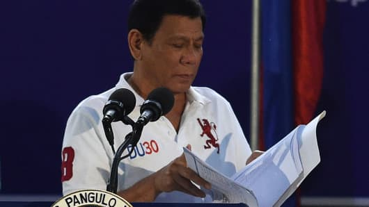 Philippine President Rodrigo Duterte looks at a folder containing the list of government officials involved in drugs as he delivers a speech before members of the Scout Rangers regiment at a military training camp in San Miguel town, Bulacan province, north of Manila on September 15, 2016.