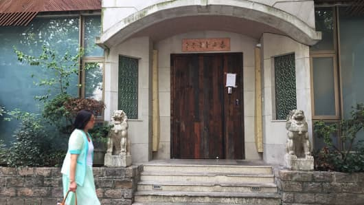 A woman walks past the closed Tai'an Table restaurant in Shanghai on September 23, 2016.