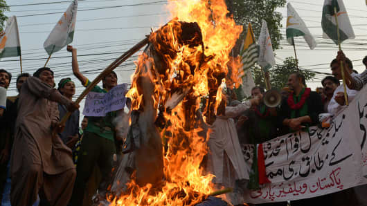 Pakistani demonstrators burn effigies of Indian Prime Minister Narendra Modi and Foreign Minister Sushma Swaraj during a protest to show solidarity with those living in Indian-administered Kashmir in Lahore on September 25, 2016.