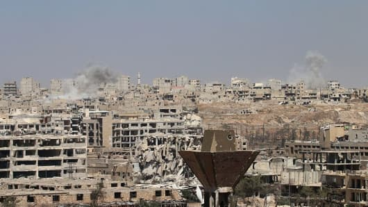 Smoke billows from buildings during an operation by Syrian government forces to retake control of the rebel-held district of Leramun, on the northwest outskirts of Aleppo, on July 26, 2016.
