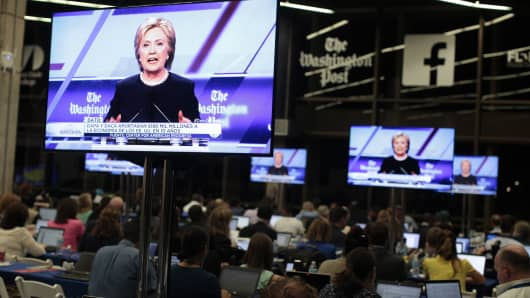 Democratic U.S. presidential candidate Hillary Clinton is shown on video screens as journalists work